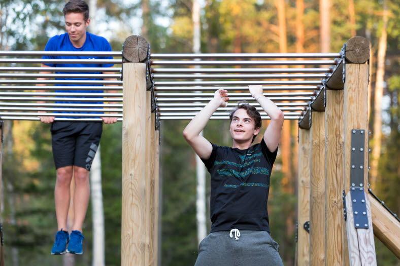 Två unga män tränar i en hinderbana vid en skog
