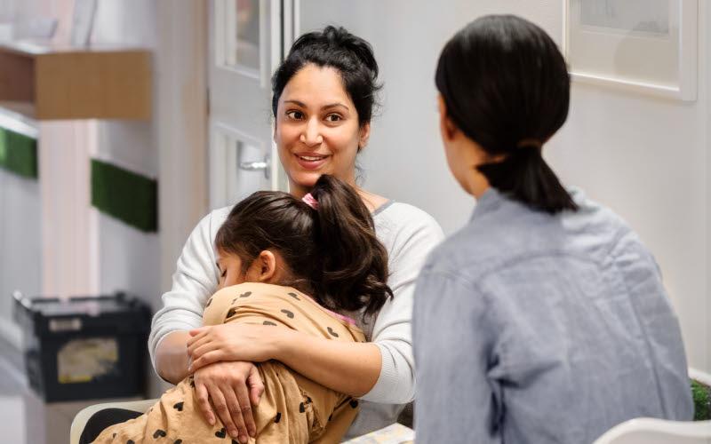 Kvinna med flicka i knäet samtalar med annan vuxen