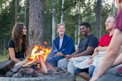 Fem ungdomar sitter ute i naturen runt en grillring med eld och skrattar