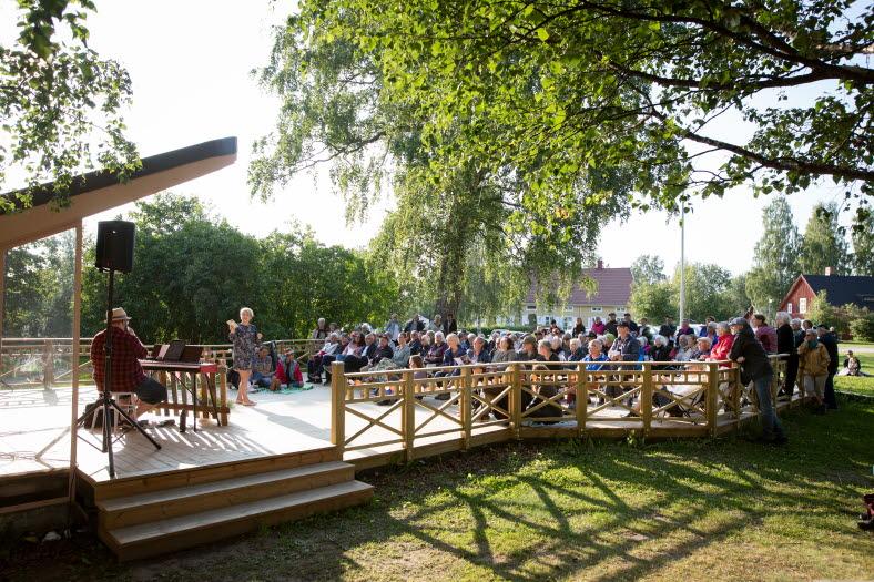 Två konstnärliga utövare håller en utomhuskonsert för publik på scenen Snäckan på Nordanå.