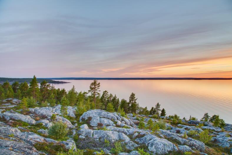 Klippor med en del grön växtlighet. Solnedgång i havet