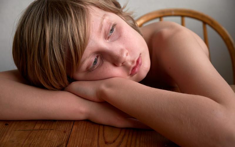 Ett sittande barn vilar sitt huvud mot bord